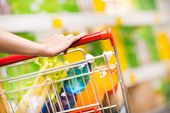 stock photo of trolley  - Woman shopping at supermarket hands on trolley close - JPG
