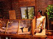 image of sauna woman  - Woman having Ayurvedic sauna treatment - JPG