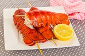 picture of lobster tail  - Three large steamed lobster tails on wooden skewers on white plate with half of lemon - JPG