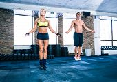 foto of jump rope  - Muscular man and beautiful sporty woman workout with jumping rope in crossfit gym - JPG