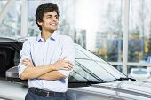 picture of showrooms  - Handsome young man standing besides car in showroom  - JPG