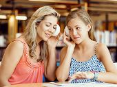 stock photo of mums  - A teenage girl with headphones sitting in a library with her mum - JPG