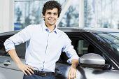 foto of showrooms  - Handsome young man standing besides car in showroom  - JPG