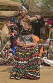 pic of rajasthani  - Rajasthani dancer in ornate black costume trimmed with beads and sequins performing at the Sarujkund Fair near Delhi in India - JPG