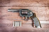 picture of revolver  - black revolver gun with bullets isolated on wooden background - JPG
