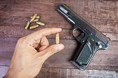 pic of semi  - hand with bullet and Semi-automatic 9mm gun on wooden background. ** Note: Shallow depth of field - JPG