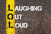 stock photo of lol  - Chat Acronym LOL as Laughing Out Loud. Yellow paint line on the road against asphalt background. Conceptual image - JPG