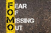 picture of missing  - Social Media Acronym FOMO as FEAR OF MISSING OUT. Yellow paint line on the road against asphalt background. Conceptual image - JPG