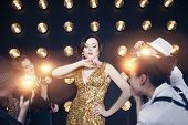picture of superstars  - Superstar woman wearing golden shining dress posing to paparazzi