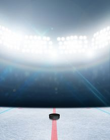 pic of illuminated  - A generic ice hockey ice rink stadium with a frozen surface and a hockey puck under illuminated floodlights - JPG