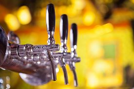 pic of tapping  - Shallow depth of field shot of beer tap machine with blurred golden background - JPG