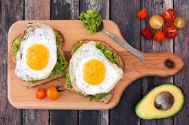 picture of whole-grain  - Avocado egg open sandwiches on whole grain bread with tomatoes on paddle board with rustic wood table - JPG