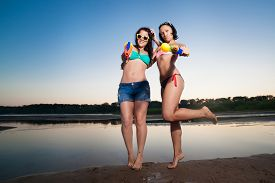 image of pistols  - Two young girl posing with water pistols - JPG