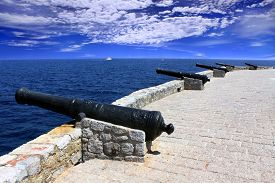 picture of hydra  - Row of old cannons aiming at the sea on the fortress Hydra island Greece - JPG