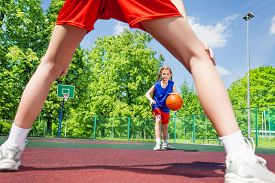 foto of legs apart  - Girl with ball view between two legs of opposite player during basketball game on the playground outside - JPG