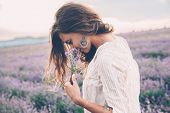 Beautiful model walking in spring or summer lavender field in sunrise backlit. Boho style clothing a poster
