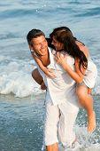 Постер, плакат: Игривый Happy позитивные выражая пара мужчин и женщин улыбаясь пешком вниз на пляж побережье