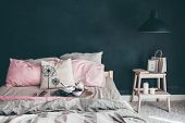 Black and pink stylish loft bedroom. Unmade bed with breakfast and reading on tray. Lamp and interio poster