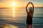 Blonde woman in summer hat stay on the coastline by sea beach with heart symbol of her hands. Sea su poster