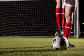 Low section of male soccer player with ball on field against goal post poster