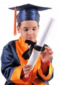 image of graduation cap  - Elementary boy wearing graduation cap and gown proudly holding his diploma - JPG