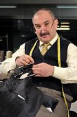 stock photo of tailoring  - Tailor with measure sewing a jacket  - JPG