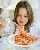 stock photo of healthy eating girl  - young girl eating spaghetti in restaurant - JPG
