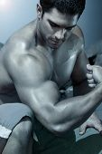 picture of body builder  - body builder flexing his arm with blue treatment - JPG