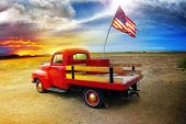 Red vintage pick up truck with American flag in wide open country side with dramatic sunset cloudsca