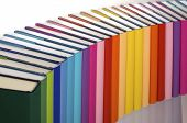 Close-up of curve aligned in rainbow colors paper wrapped books with blank spine facing front, view