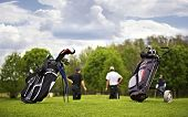 foto of golf bag  - Two golf bags standing in front of a group of golf players putting on green - JPG
