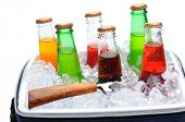 Assorted soda bottles in a cooler full of ice with bottle opener. Horizontal format over white.