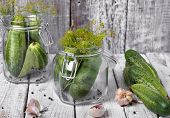 Preserved Cucumbers In Glass Jars With Garlic And Dill On Table poster