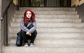Homeless Girl, Young Beautiful Red Hair Girl Sitting Alone Outdoors On The Stairs Of The Building Wi poster