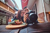 Happy Chinese Couple Sitting At Cafe Outside Enjoying Traditional Asian Food And Watching Pictures I poster