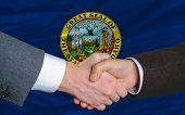In Front Of American State Flag Of Idaho Two Businessmen Handshake After Good Deal
