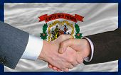 In Front Of American State Flag Of West Virginia Two Businessmen Handshake After Good Deal