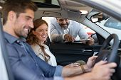 Cheerful young couple looking around in new car at showroom while car dealer explaining the features poster