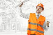 The Builder In A Construction Vest And Orange Helmet Smiling As Winner Against Industrial Background poster