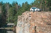 Woman Relaxing Standing At Edge Of The Cliff Near Lake. Suv Car. Travel Concept poster
