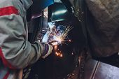 Professional Repairman Worker In Automotive Industry Welding Metal Body Car With Sparks. poster