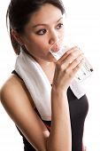 foto of asian woman  - An isolated shot of a beautiful asian woman drinking water after exercising - JPG