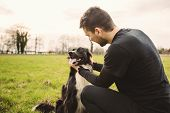 Man Dog Playing Outdoor In The Park. Young Owner Hugs His Pet. Friendship Between Owner And Dog. Ani poster