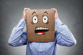 Businessman with cardboard box on his head showing a shocked and surprised expression expression con poster