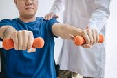 Doctor Physiotherapist Assisting A Male Patient While Giving Exercising Treatment On Stretching His poster
