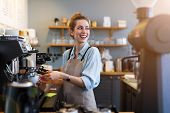 Young barista preparing coffee for customers at her cafe counter poster