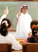 Arabic Muslim teacher in classroom with children. Competition and success.