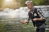 Mature man fly fishing in beautiful river poster