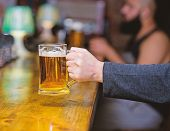 Glass With Fresh Lager Draft Beer With Foam. Male Hand Holds Mug Filled With Cold Tasty Beer In Bar. poster