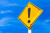 Caution Yellow Road Sign With Exclamation Mark Above Blue Sky poster